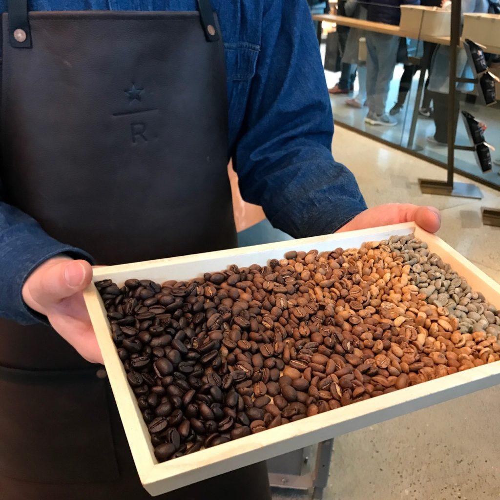 STARBUCKS RESERVE ROASTERY TOKYOでコーヒー豆を見せてくれるお兄さん